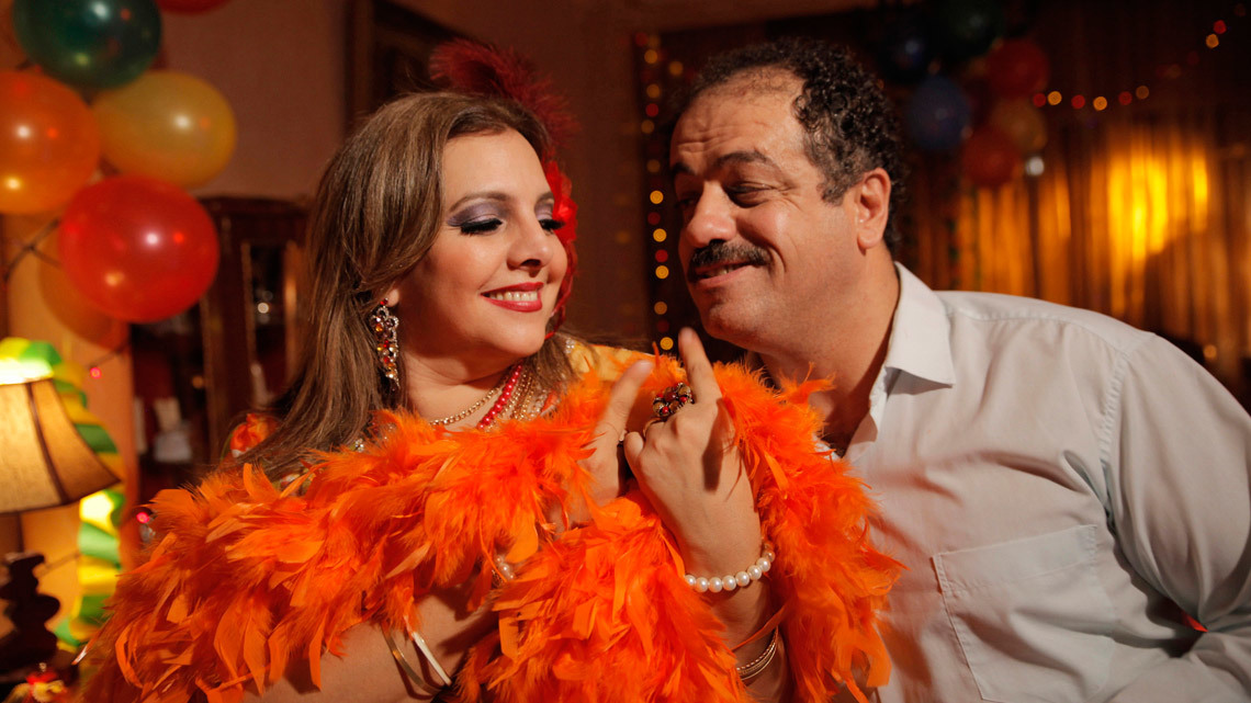 A woman with an orange feather boa and man in a room with balloons