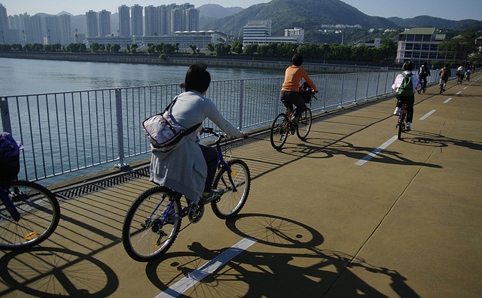 Cyclists cycling along the sea front in Tai Wai
