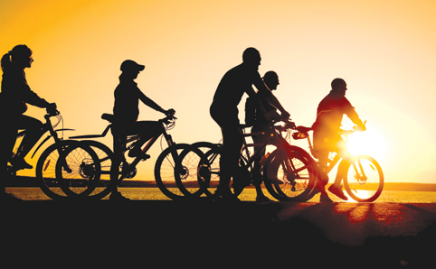 Silhouettes of cyclers set against a sunset