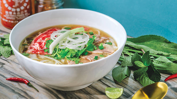 Bowl of beef pho with noodles and herbs