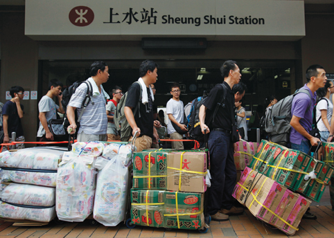 Pearl River Delta Megacity - Tourists with large bundles of goods and boxes near Sheung Shui Station