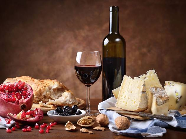 A table topped with a platter of cheese, a bottle and glass of red wine, crusty white bread, an open pomegranate, fruit paste and nuts
