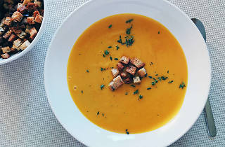 A bowl of orange-coloured soup with croutons on top