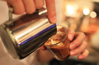 Shot of barista pour milk into coffee
