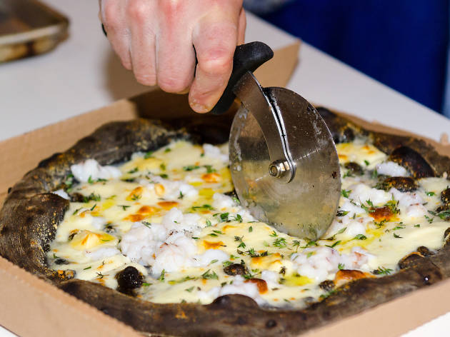 Black pizza topped with lobster and cheese being cut