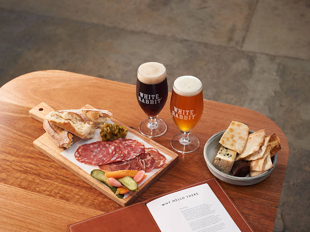 Two beers on a wooden table with a charcuterie platter