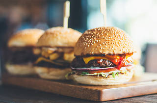 Three burgers on a wooden board