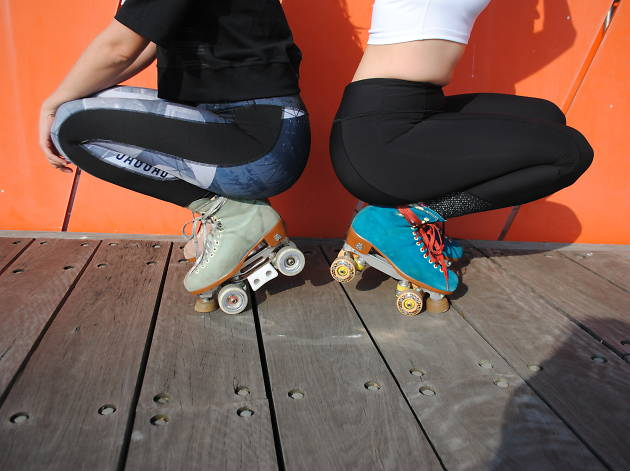 Two women wearing rollerskates
