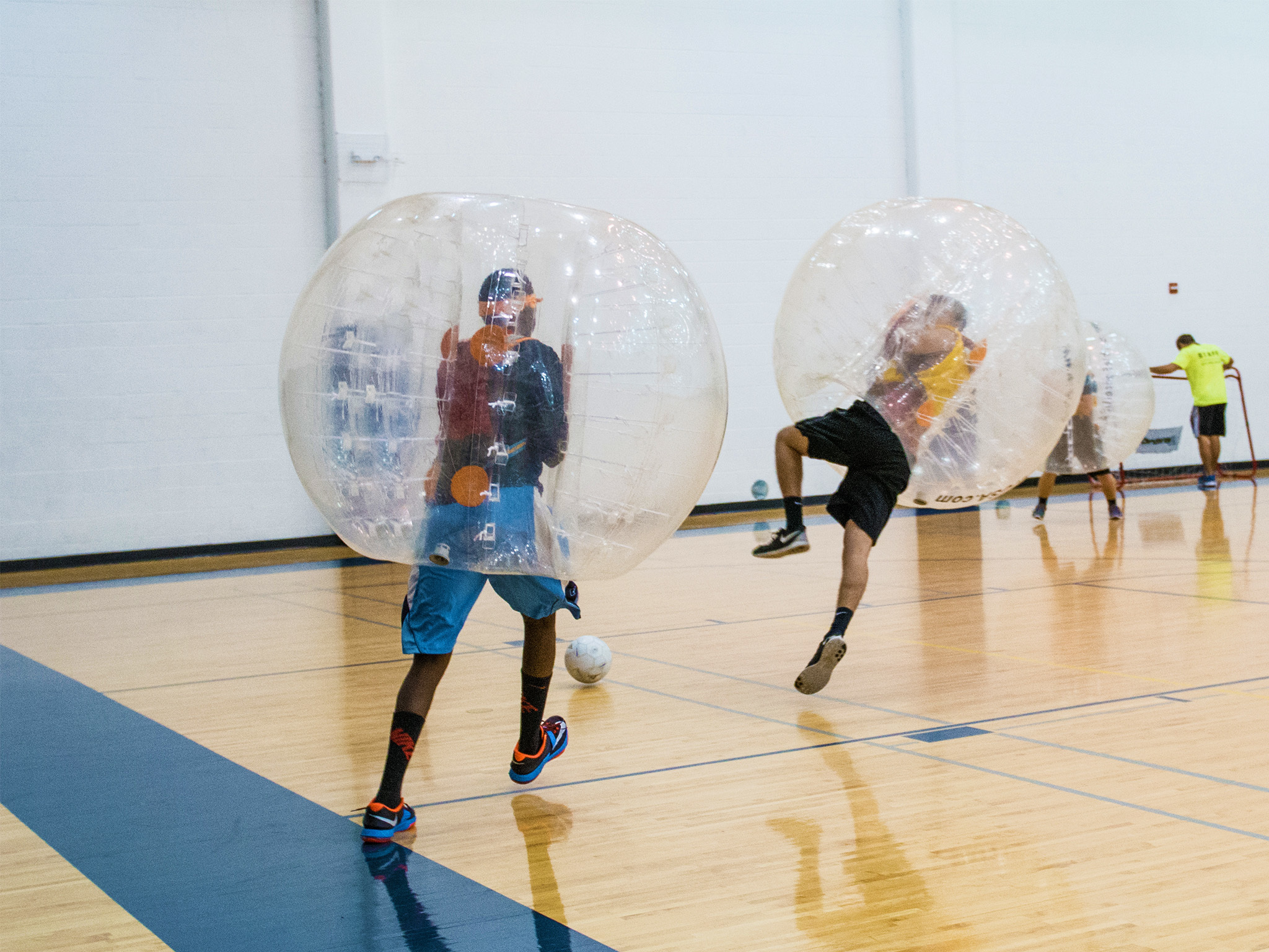 People dressed in bubbles playing football