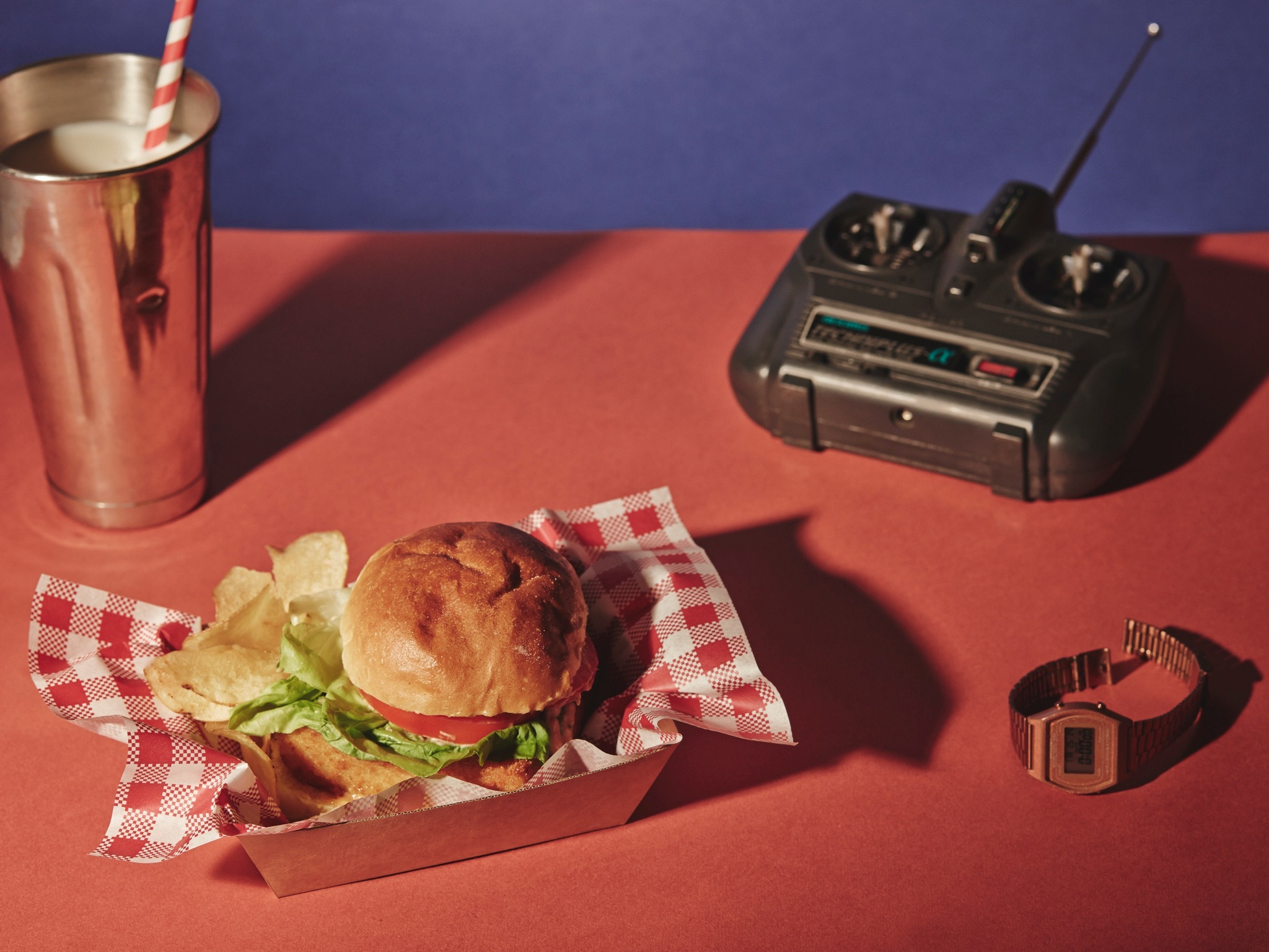 Photograph of a mac and cheese burger, milkshake in a silver shaker with a stripy straw, a vintage watch and a vintage radio, all set on a red tabletop