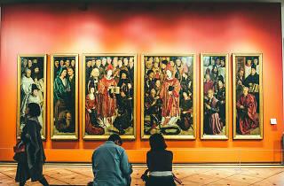 Pessoas sentadas observam um painel no Museu de Arte Antiga