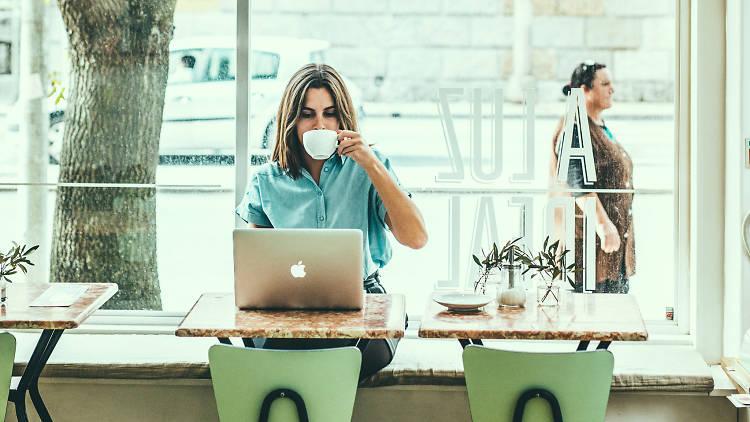 Uma senhora bebe um café num café em Lisboa