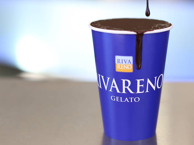 A blue RivaReno cup full of thick, dark hot chocolate dripping down the sides