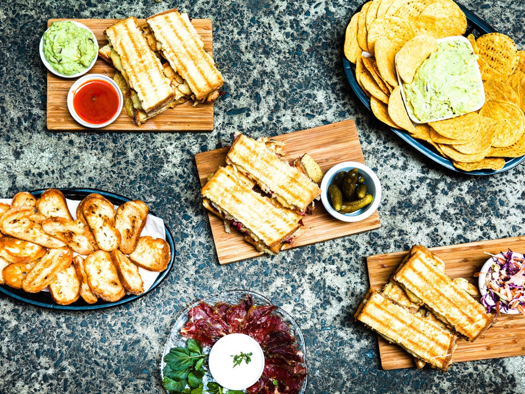 toasties, cornchips and guacamole on a table