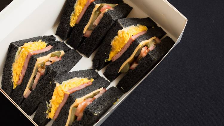 Bamboo charcoal bread sandwiches in takeout box