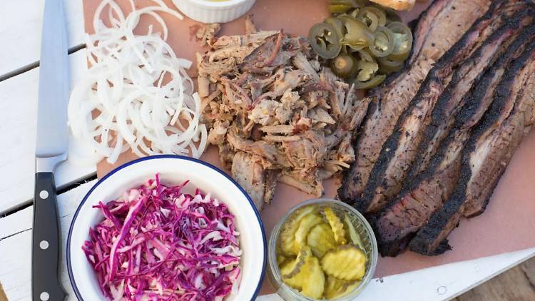 Tray of American barbecue: brisket, pulled pork, pickles and bread