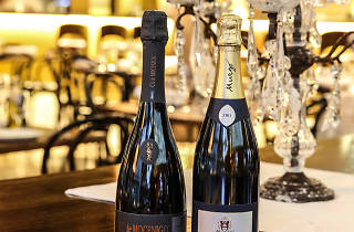 Two bottles of sparkling wine sit on a table with a candelabra and a plate of cured meats
