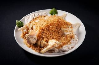 chicken dish with head and fried garlic on top