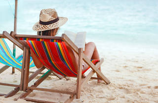 Dona llegint a la platja