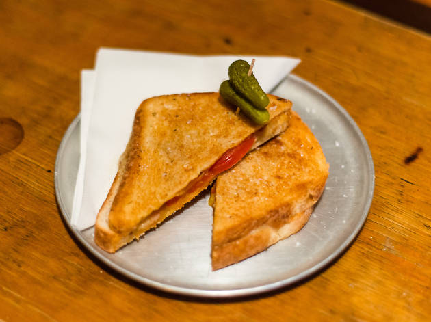 A toasted sandwich on a metal plate with pickles on top