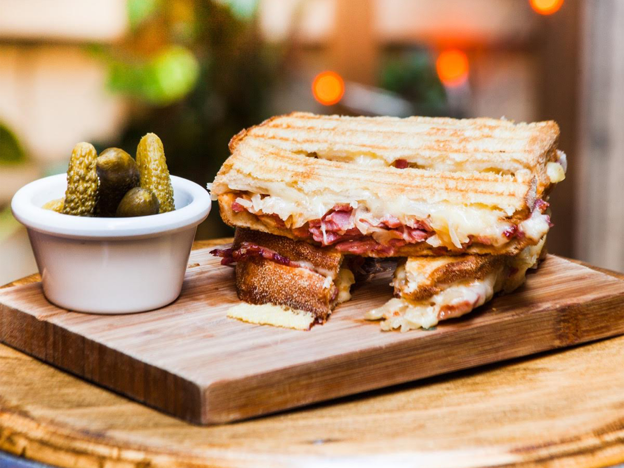 A toasted sandwich on a wooden board with a side of pickles