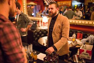 A bearded man talks to visitors at a tasting stall