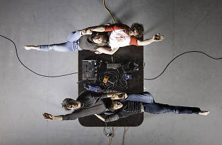 Four dancers lie across a large black object on a stage