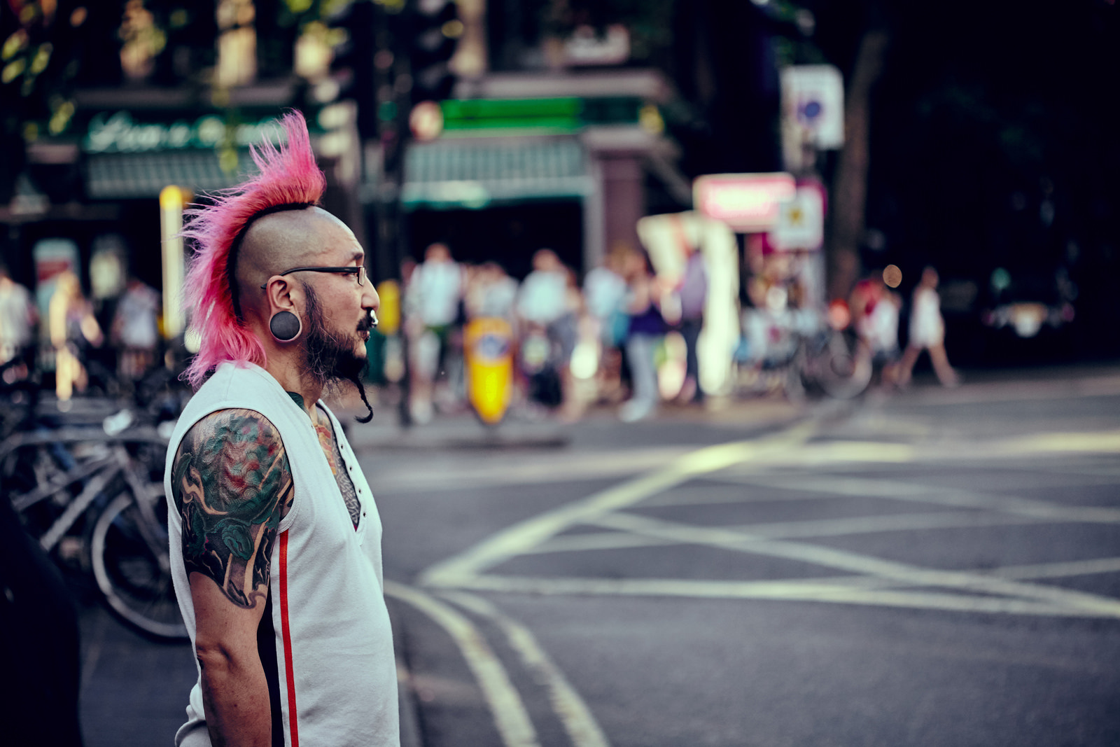 A punk with tattoo and a pink mohawk in Soho
