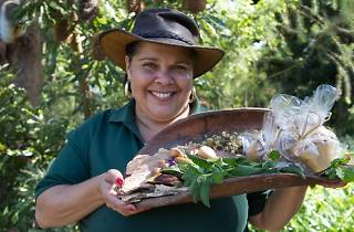 Jody Orcher smiles into the camera, holding a curving shield filled with fresh produce