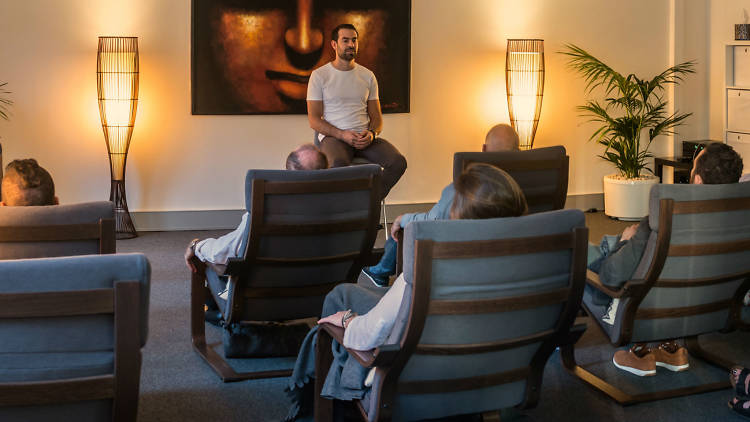 People sitting on chairs meditating