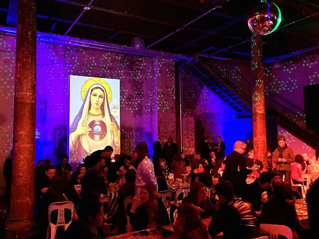 People dining beneath an image of the Virgin Mary