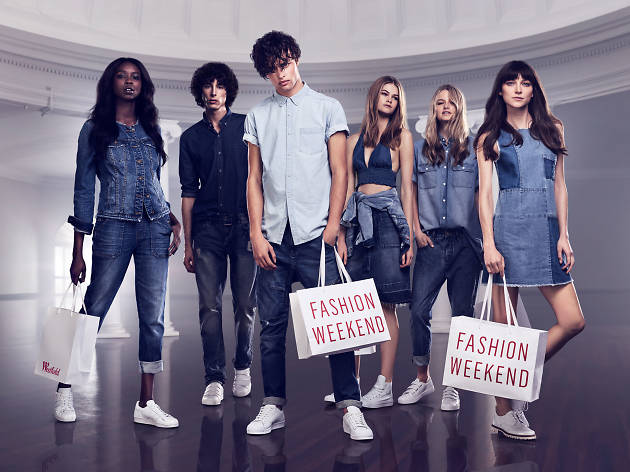 Models pose with bags saying 'Fashion Weekend'
