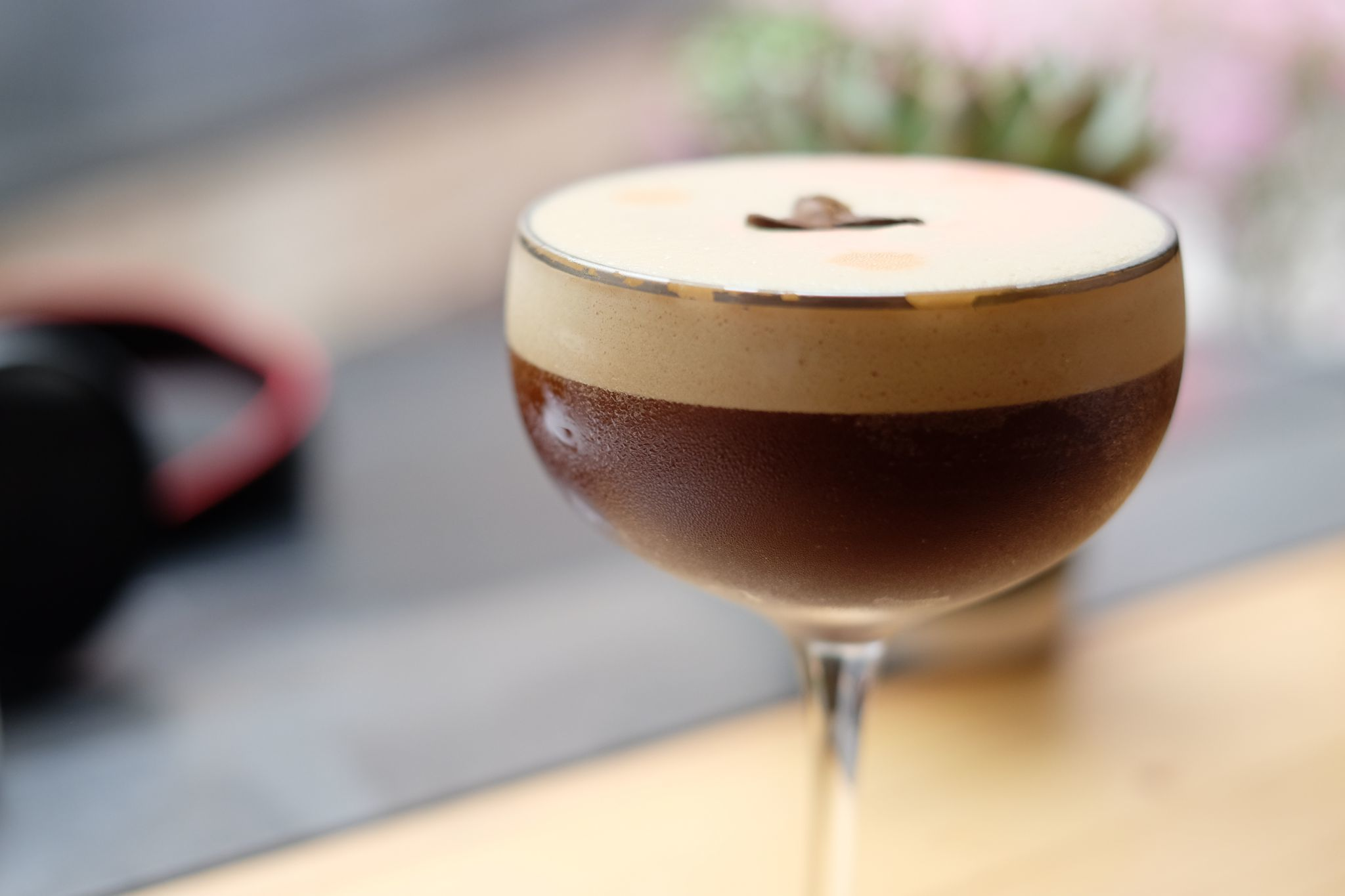Espresso martini in flat champagne glass with froth garnished with coffee beans