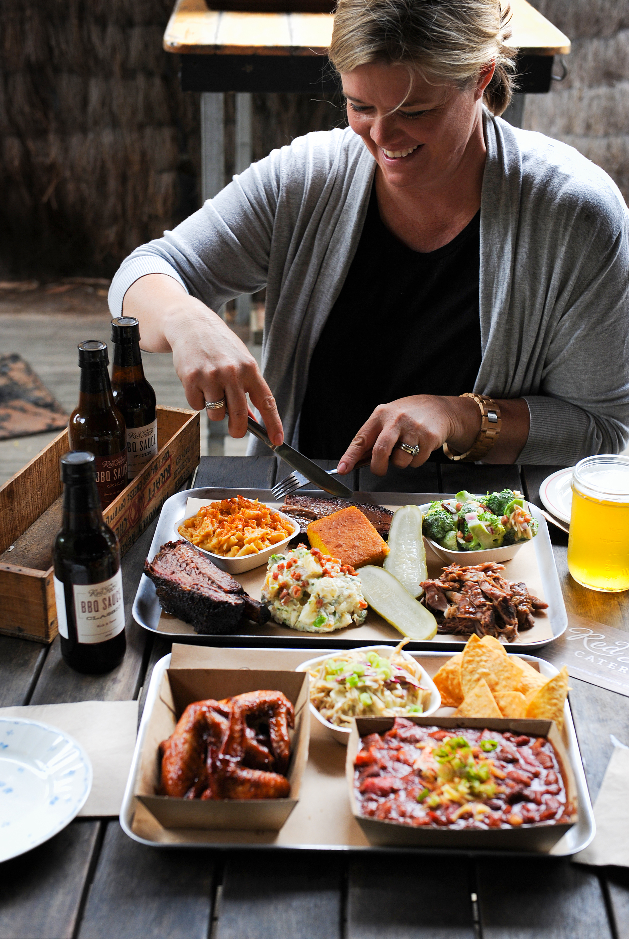 A woman holds a knife and fork over two plates of barbecue and sides
