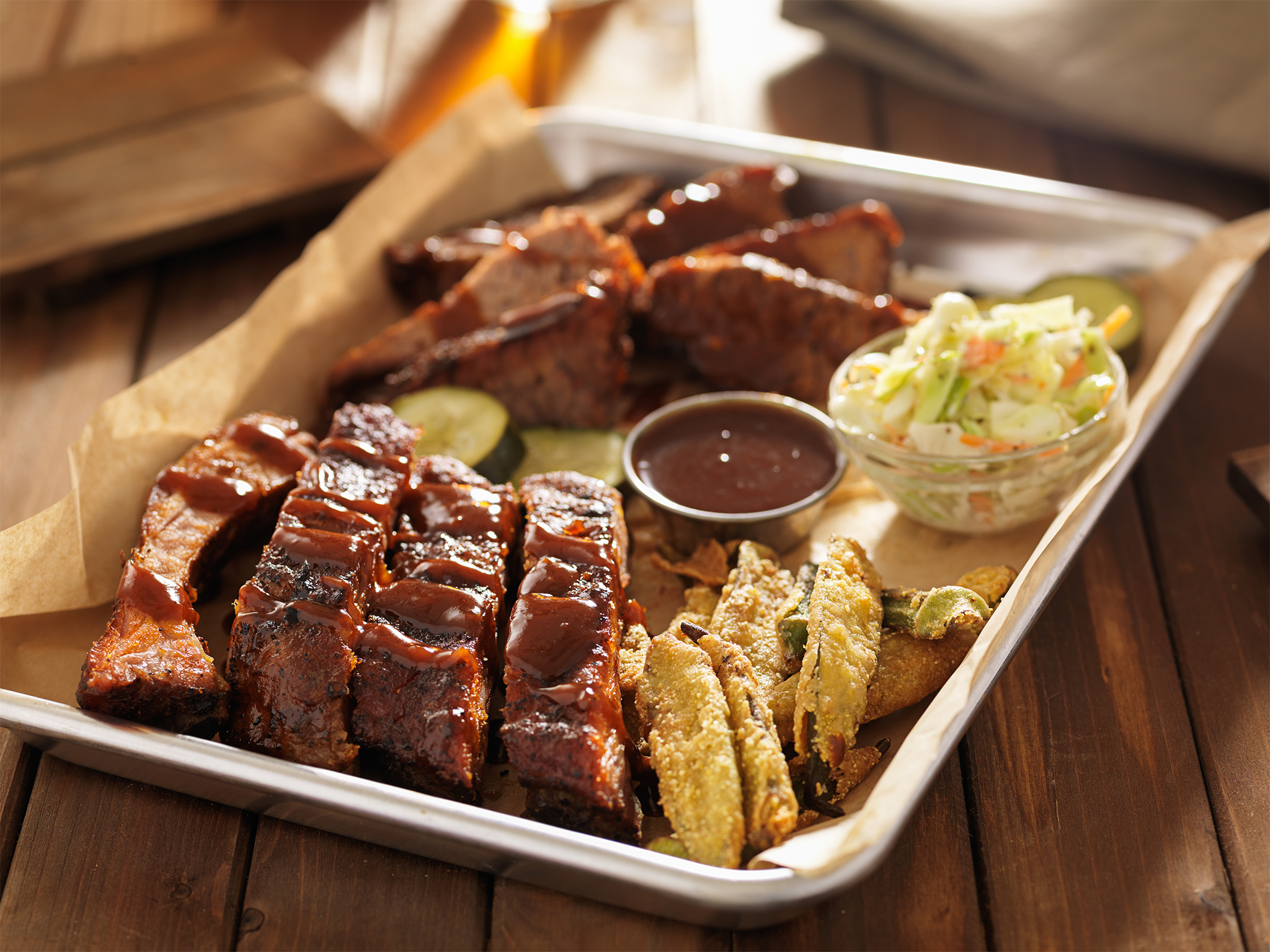 Note: This image was not taken at the featured venue. barbecue ribs with brisket, fried okrra and  cole slaw on tray