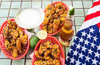 Three baskets of fried chicken wings, a Margarita and a bottle of hot sauce
