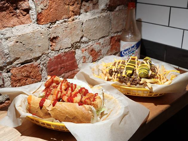 Po'boys on two trays covered in mayo