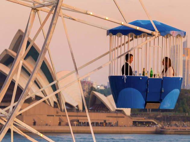 A couple on the ferris wheel with the Opera House in the background