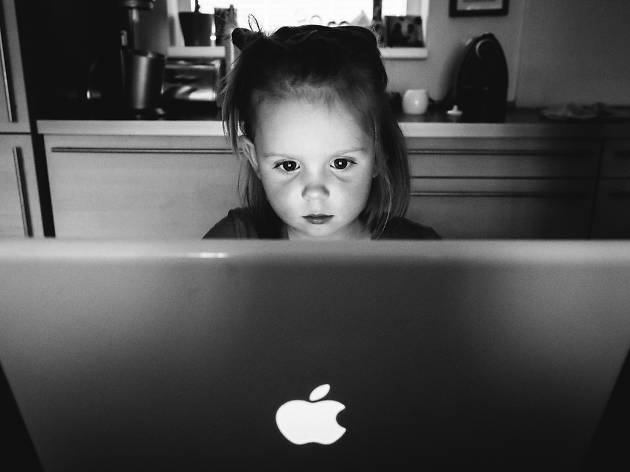 Girl sitting at a computer in the dark