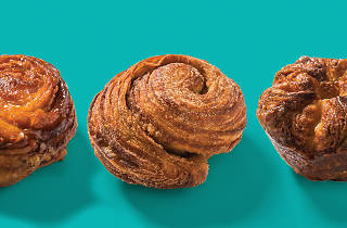 Three kouign amanns on a turquoise background