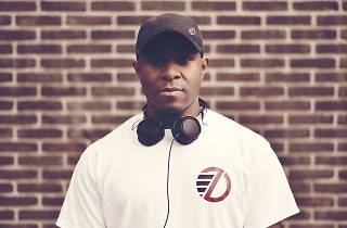 DJ EZ stands in front of a brick wall