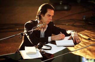 Nick Cave sitting at a piano, writing