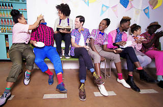 A group of 8 people sitting on a bench, all wearing very colourful Social Studio clothes