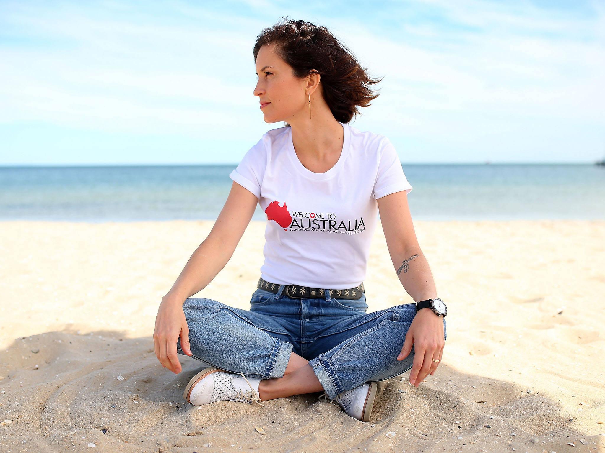 Missy Higgins sitting cross-legged on the beach