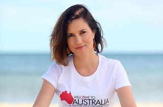 Missy Higgins sitting on a beach