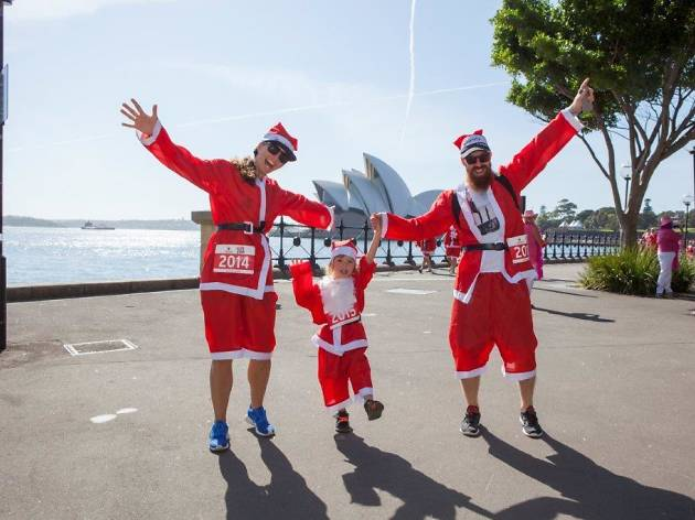 Two men and a child wearing santa costumes during the course
