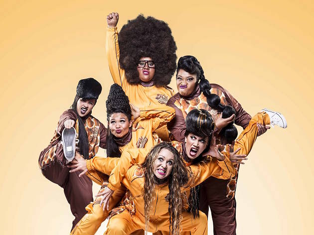 A group of women in matching orange outfits, posing to the camera