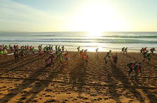 People walking on the beach at sunrise