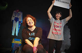 Two women, one sitting in a wheelchair, the other standing and holding a sign which reads 'Swearing'