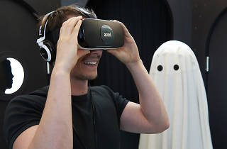 Man holding a virtual reality headset with a white-sheeted 'ghost' in the background